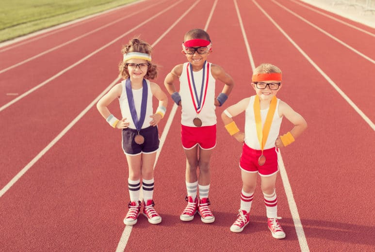 Children wearing medals at a track