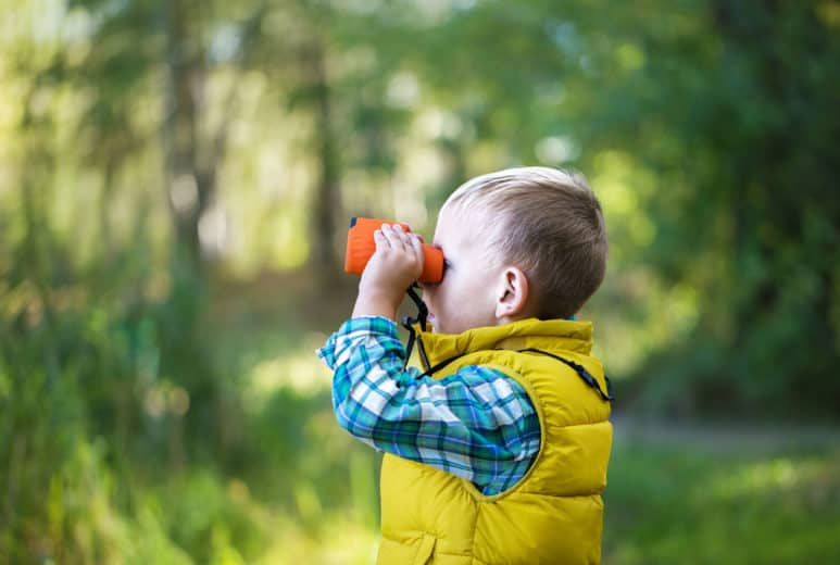 Young boy looking exploring with binoculars