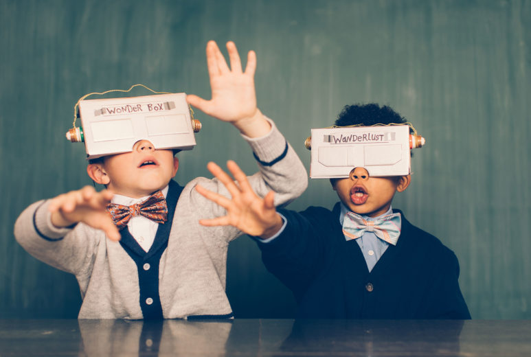 Two young boys wiht pretend virtual reality headsets on