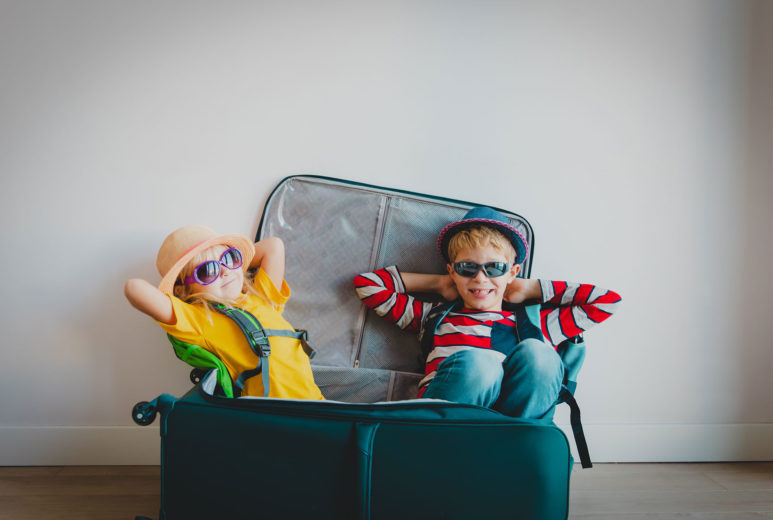 Happy boy and girl wearing sunglasses sitting in a suitcase